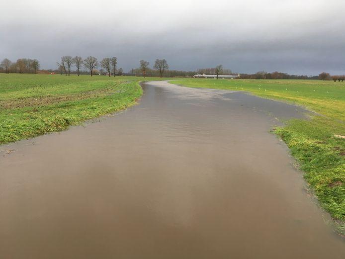 Grote foto: de Baakse Beek zit tot het randje vol met water. Kleine foto: stuw Vragenderpoort in Lichtenvoorde heeft moeite met al het water.