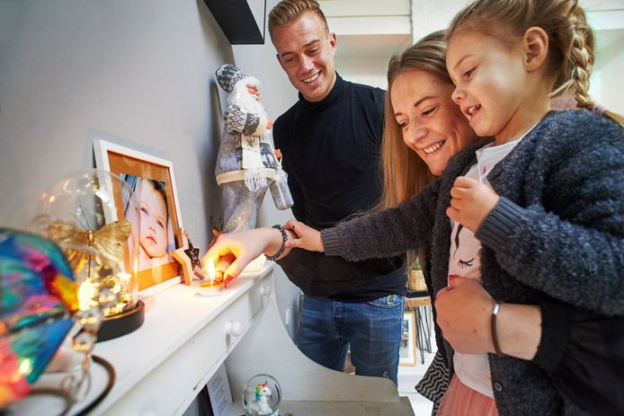 De ouders en zusje van de overleden Eva Blijleven-Timmermans uit Uden steken een kaarsje aan bij het herdenkingshoekje in de woonkamer.