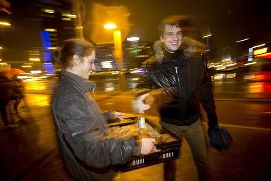 Een feestvierder neemt een gratis oliebol bij de Erasmusbrug in Rotterdam.