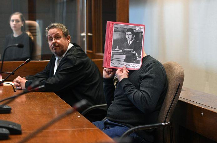 Jörg L. houdt een map voor zijn gezicht, terwijl zijn advocaat toekijkt, bij de start van het proces bij de regionale rechtbank van Keulen.