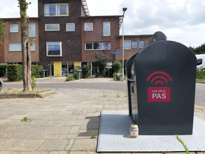 Restafvalcontainer aan de Simon Vestdijksingel in de Arnhemse wijk Rijkerswoerd, met eenzaam achtergelaten glazen potje dat goed door de zwerfvuilopening had gepast.