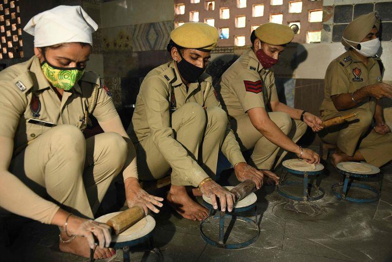 Agenten rollen chapati's bestemd voor covid-19-patiënten in de Indiase stad Amritsar. Gedurende de lockdown deelt de politie in de deelstaat Punjab voedsel uit aan arme Indiërs.  Beeld AFP