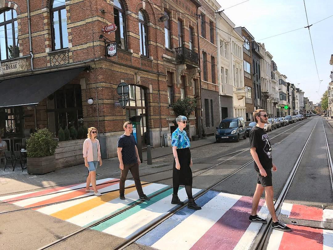 Werknemers van Het Roze Huis op één van de regenboogzebrapaden in Antwerpen.