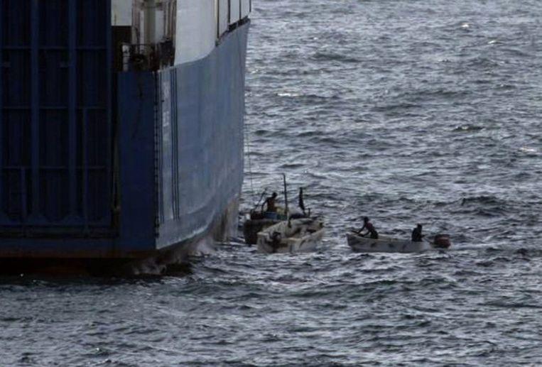 Somalische piraten schipperen langs de gekaapte 'Faina'. Foto AP/U.S. Navy Beeld