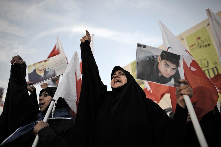 Een Bahreinse vrouw houdt een portret omhoog van een opgepakte politieke activist in een antiregeringsdemonstratie.  Beeld AFP