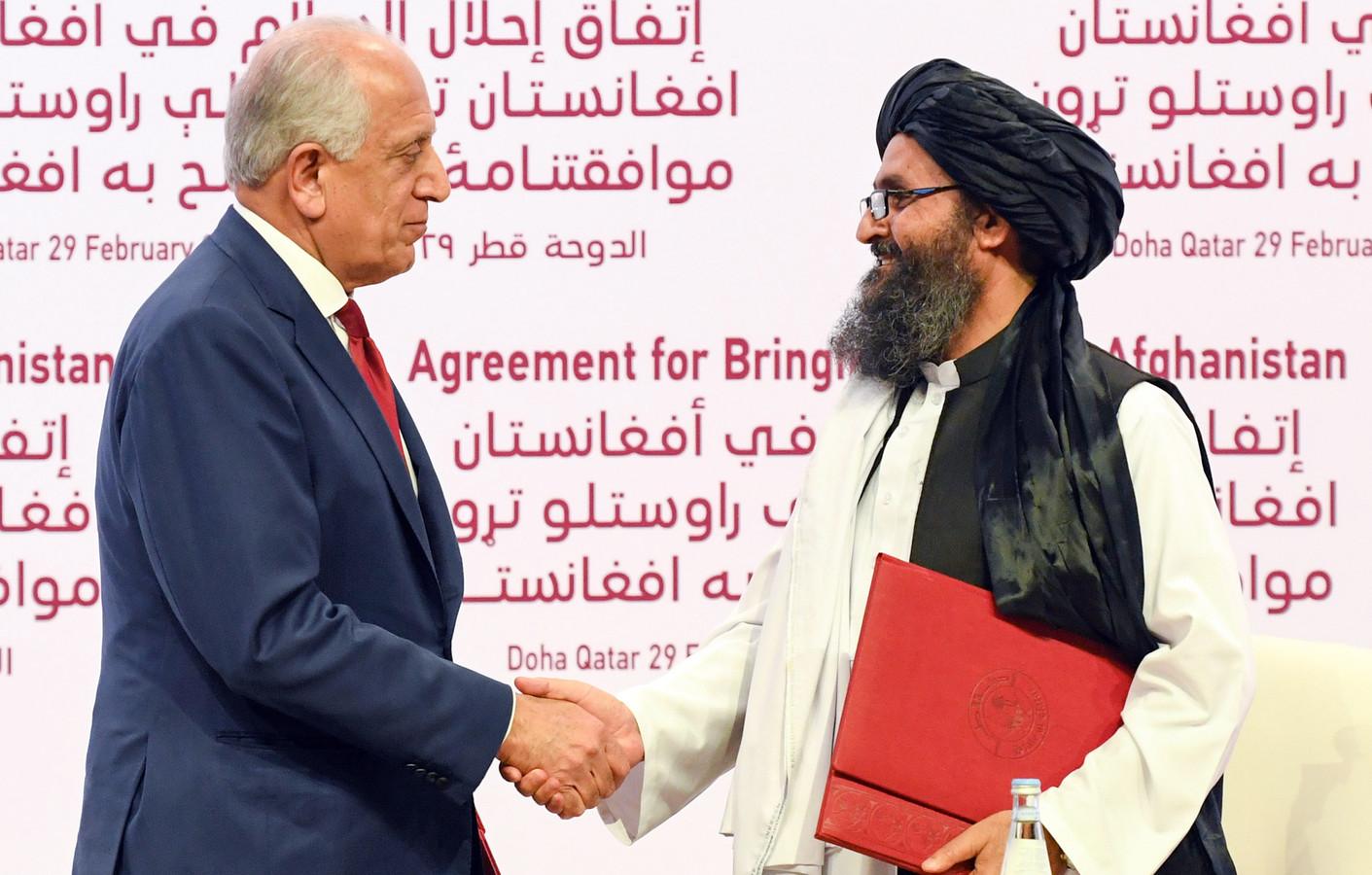 Amerikaans gezant Zalmay Khalilzad (links) en talibanleider Abdul Ghani Baradar bij de ondertekening van een vredesakkoord op 29 februari 2020