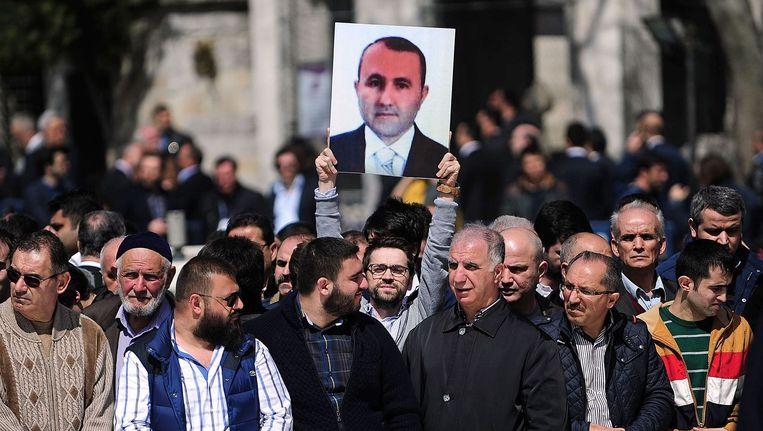 Mensen houden het portret omhoog van de overleden Mehmet Selim Kiraz, in Istanbul. Beeld afp