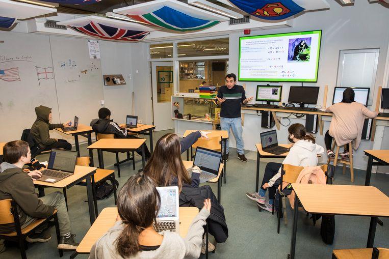 De klas van wiskundeleraar Kamuran Dinc is verdeeld over twee lokalen.  Beeld Dingena Mol