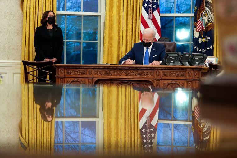 Joe Biden ondertekent meerdere decreten in het Oval Office. Beeld EPA