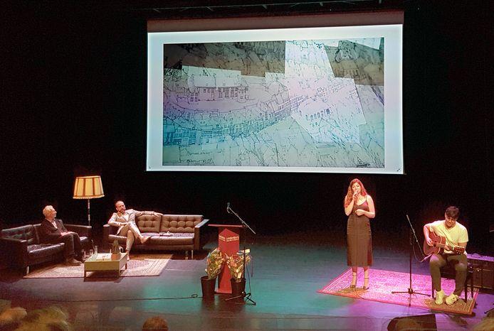 Tekenaar Ben Luderer (links op de bank) en de zangeres Linde Schöne kregen de Karel de Grote Oeuvreprijs 2020 en de Cultuur Stimuleringsprijs Stad Nijmegen uitgereikt door burgemeester Bruls in de Lindenberg. Linde Schöne zong er enkele nummers.