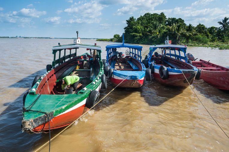 Met kleurrijke tentbootjes kun je vaartochten maken over de Surinamerivier, die bij Paramaribo uitmondt in de Atlantische Oceaan.  Beeld Alamy Stock Photo