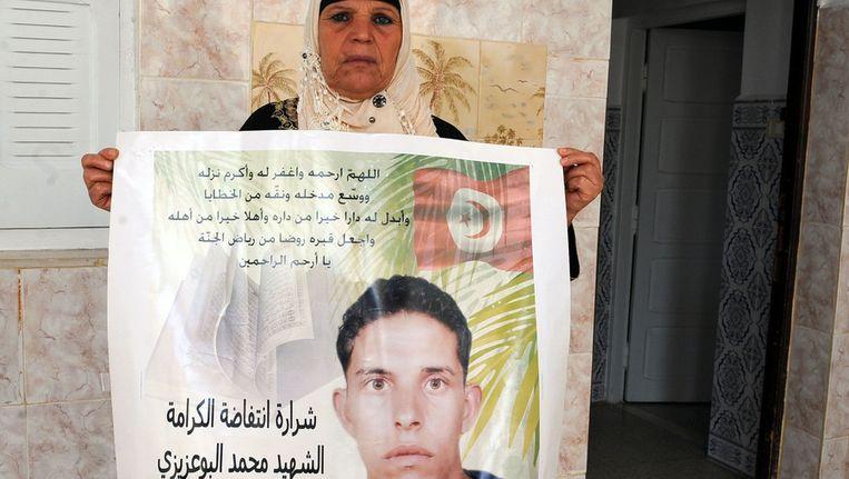 De moeder van Mohamed Bouazizi met een afbeelding van haar zoon. © AFP Beeld