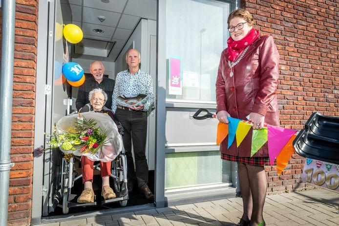 Mevrouw van Hout-Vereijken  is 100 jaar geworden. Achter haar: zonen Peter en Mari (rechts). Rechts van de jarige burgemeester Greet Buter.