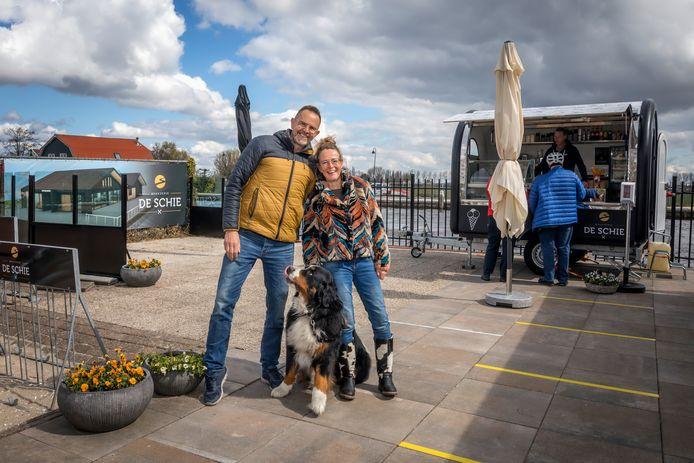 Andre de Jong en Mirjam Lammerse met hond Bo, voor hun foodtruck. Op de achtergrond een impressie van Brasserie De Schie.