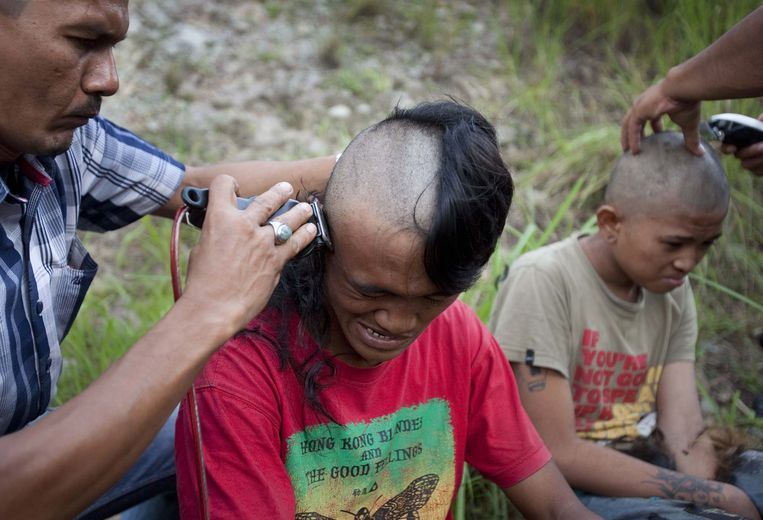 In this photograph taken on December 13, 2011 police shave the hair of detained Indonesian punks at a police school in Aceh Besar in Aceh province. Sharia police are