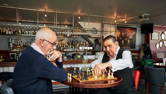 Kroegbaas Ger Koedam (rechts) en Gerrit Markus van schaakclub SO Rotterdam spelen een partij schaak in Café Ari.
