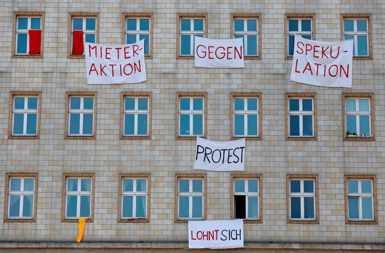 Spandoeken waarmee huurders aan de Karl-Marx-Allee demonstreren tegen speculatie met huurwoningen.  Beeld AFP