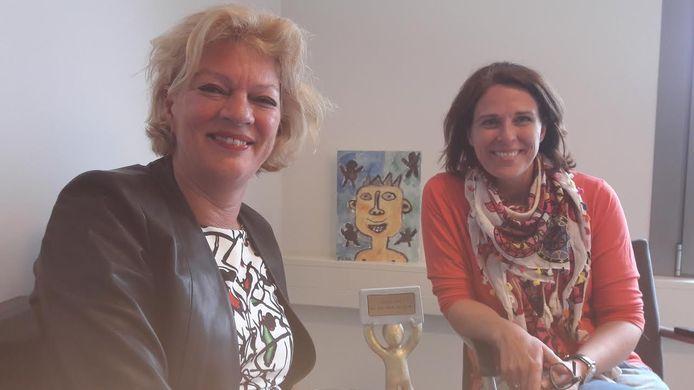 Mietske van Hooff (links) en Rianne van den Boogaart. In het midden het beeldje dat hoort bij de eretitel 'Gouden Held 2017'.