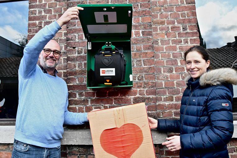 Directeur Luc Beyens en initiatiefneemster Heidi Vanslembrouck tonen het AED-toestel.