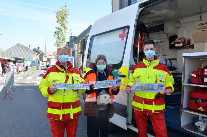 Linda De Smedt, Emilienne Schelfhout en Tibo Van Den Berge van het Rode Kruis Denderleeuw-Haaltert delen de eerste stickers uit op de markt in Welle.