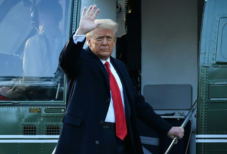 Een laatste groet van voormalig president Donald Trump, voordat hij aan boord gaat van de legerhelikopter Marine One voor zijn vertrek uit het Witte Huis afgelopen woensdag. Beeld AFP