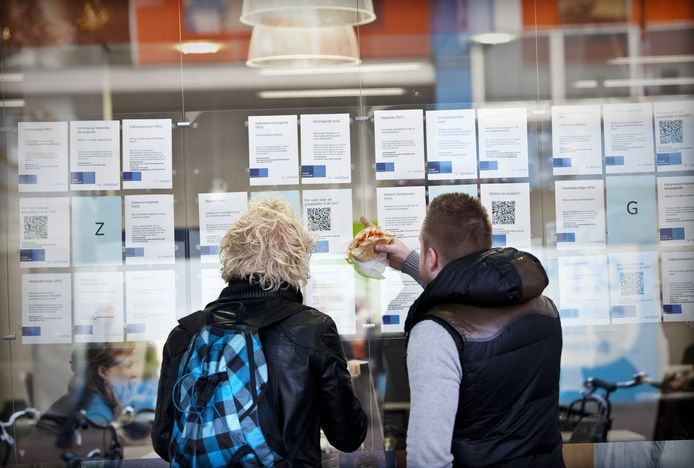 Twee belangstellenden bekijken de etalage van een uitzendbureau. De werkloosheid in Nederland is ten opzichte van een jaar geleden gestegen.