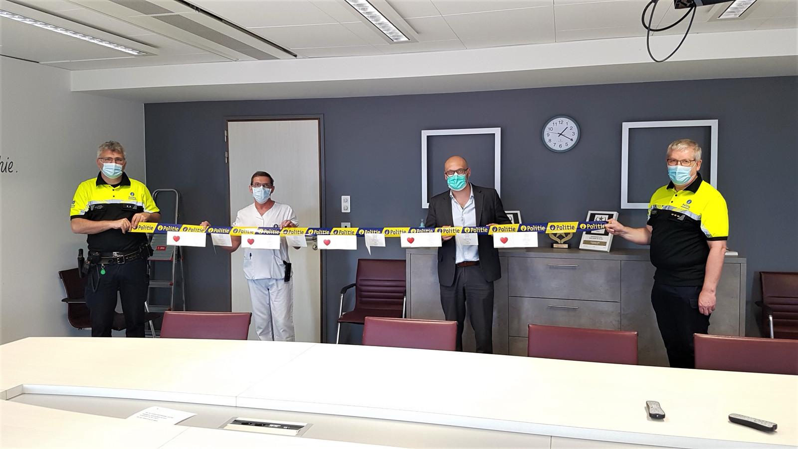 Wijkagent Luk Struyfs (links) en korpschef Dirk Van Aerschot (rechts) overhandigen enkele kaartjes aan Francis Hannes, hoofdverpleegkundige op intensieve zorgen, en directeur Jan Flament.