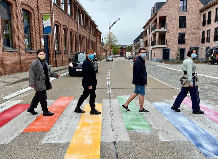 Vier scholieren uit het Sint-Jan Berchmanscollege steken over via het nieuwe regenboogzebrapad, waar ze voor geijverd hebben
