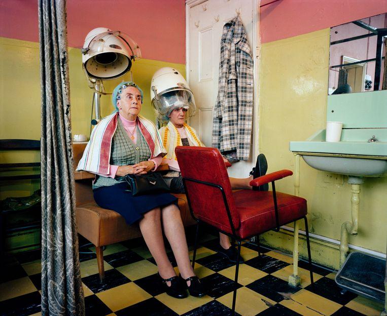 Twee vrouwen laten hunhaardos weer pico bello maken in een kapsalon in Salford, 1986. Beeld ©Martin Parr / Magnum Photos