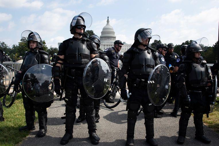 Politieagenten met schilden en rellenuitrusting staan klaar bij het Capitool, waar zaterdag maar een paar honderd pro-Trump-demonstranten komen opdagen.   Beeld EPA