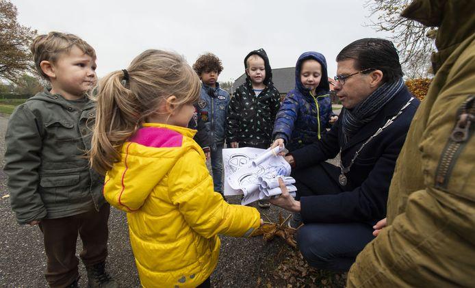 Kinderen van de peuterspeelzaal en groep 1 en 2 in Noordijk brengen tekeningen voor Sinterklaas naar burgemeester Joost van Oostrum die even verderop woont.