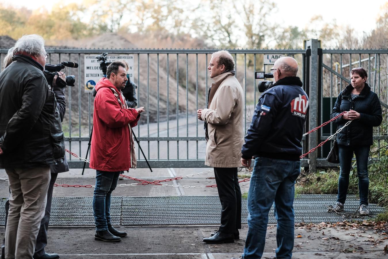 Joris Bengevoord (lichte jas), burgemeester van Winterswijk, in gesprek met een lid van de SP bij het zanddepot vlakbij de kleiput. Enkele actievoerders wilden woensdagmiddag de aanvoerweg blokkeren.