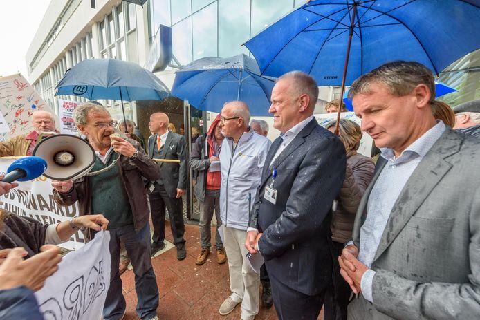 ZGT-topman Ruikes (midden in pak) liet de aanbieders van de handtekeningen aanvankelijk buiten in de regen staan.