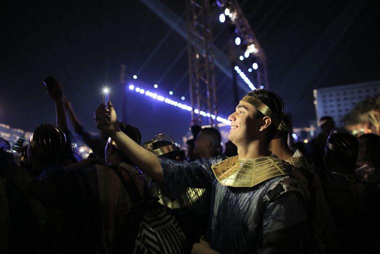 Een artiest in een kostuum uit de Egyptische oudheid neemt een selfie na de parade van 22 Egyptische mummies in de hoofdstad Caïro.  Beeld AFP