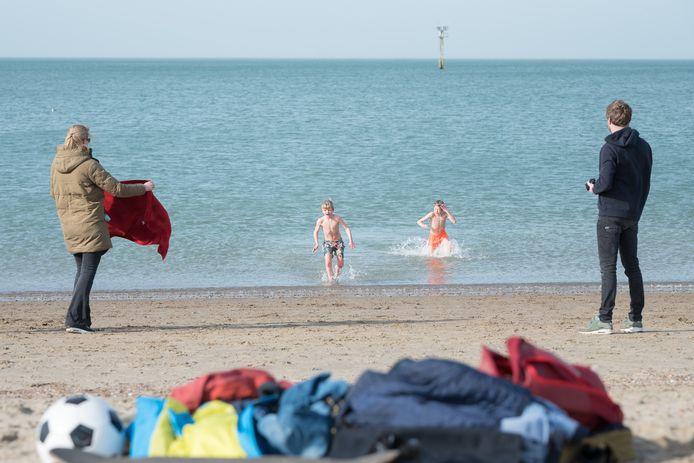 Jasper en Dafne Leunk uit Zeist vangen hun kinderen Bauke (links) en Friso op die bij de Brouwersdam een ijskoude duik in de zee hebben genomen.
