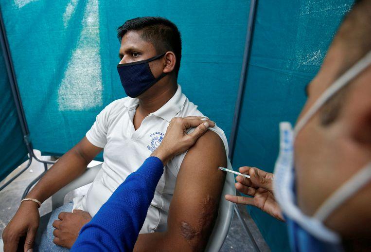 Een politieman ontvangt een dosis van Covishield, een coronavaccin van het Serum Instituut van India.  Beeld Reuters