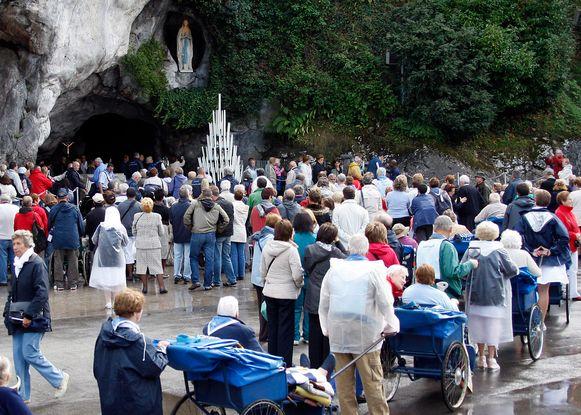 Bedevaarders wachten in de rij voor de grot van Lourdes. (Foto uit 2008)