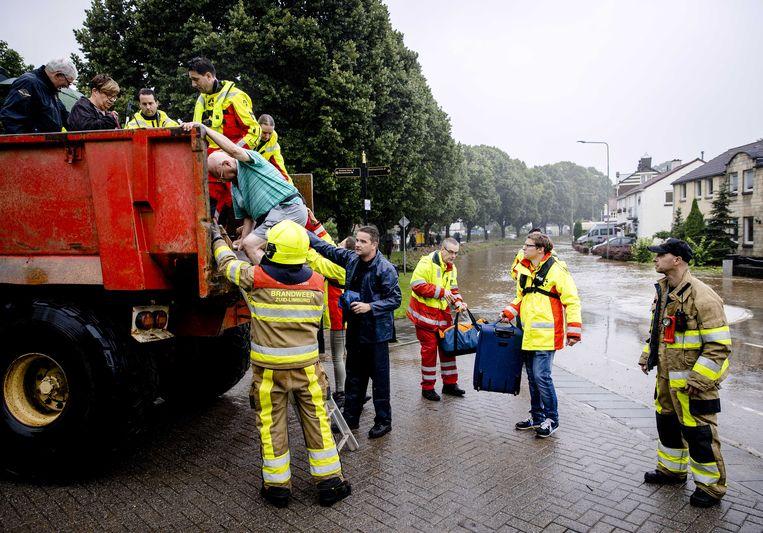 Brandweer helpt met de evacuatie van mensen uit hun woningen door de wateroverlast in Zuid-Limburg.  Beeld ANP