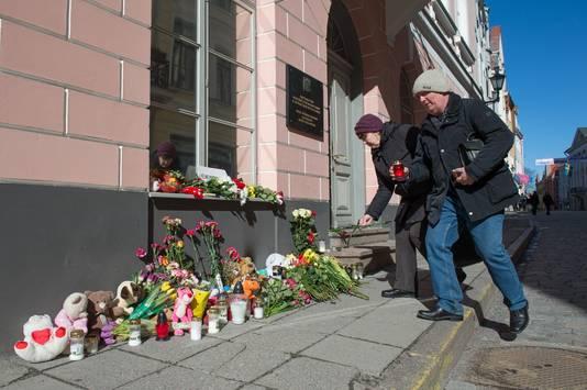 Mensen brengen bloemen  naar de Russische ambassade.