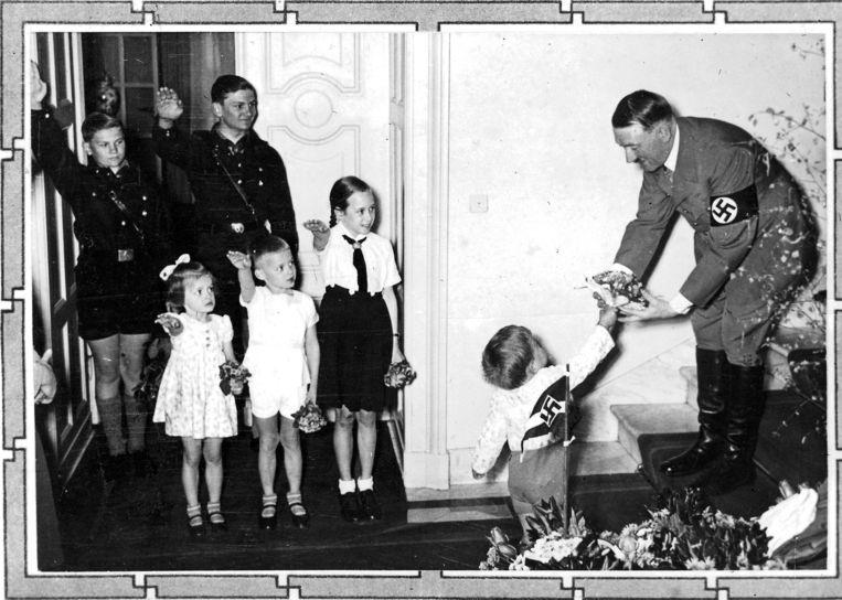 Een jongetje geeft Adolf Hitler een boeketje bloemen voor zijn 50ste verjaardag op 20 april 1939.  Beeld Sueddeutsche Zeitung Photo
