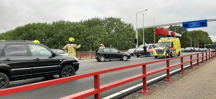 Terwijl brandweerlieden een beknelde automobiliste bevrijden, komt een ambulance ter plaatse op de Sloebrug.