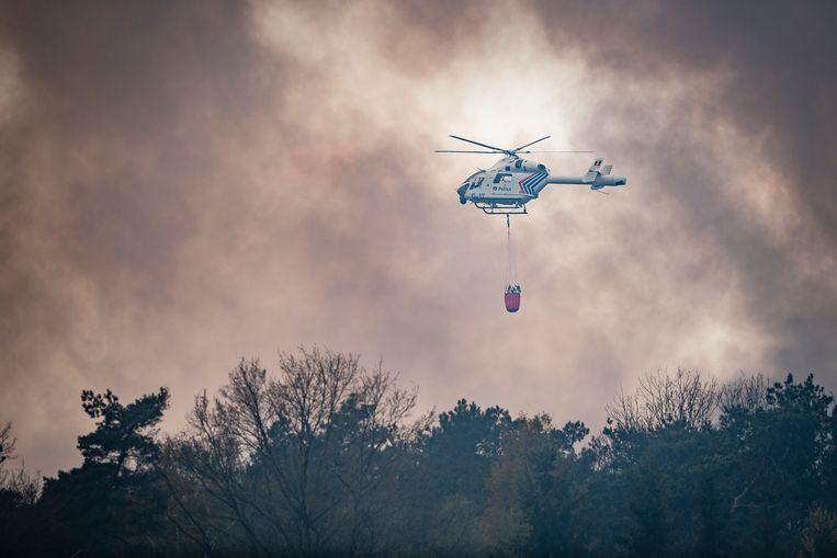 Om de gigantische brand te blussen werden helikopters ingezet. Ook de Nederlandse Koninklijke Luchtmacht kwam meeblussen.  Beeld Gregory Van Gansen / Photo News