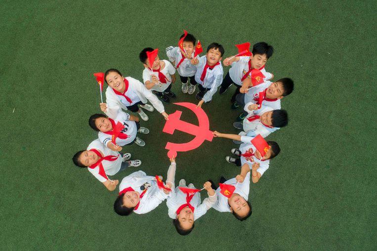 Scholieren in Taizhou vieren de 99ste verjaardag  van de Chinese Communistische Partij.  Beeld Getty