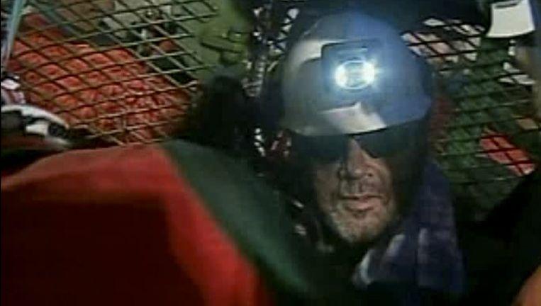 Een historisch moment: Luis Urzua, ploegbaas en rots in de branding tijdens de maandenlange opsluiting, wordt als laatste gered. Beeld UNKNOWN