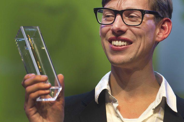Simon van der Geest neemt zijn Gouden Griffel in ontvangst. Hij schrijft dit jaar het Kinderboekenweekgeschenk. Beeld ANP