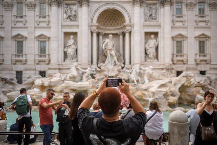 Toeristen maken foto's aan de Trevifontein in Rome