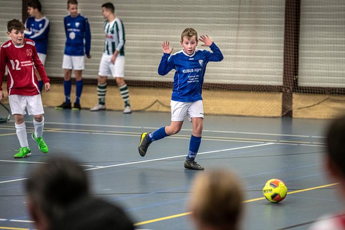 Een jeugdspeler van Woezik is zich van geen kwaad bewust in zijn wedstrijd tegen leeftijdsgenoten van Alverna.