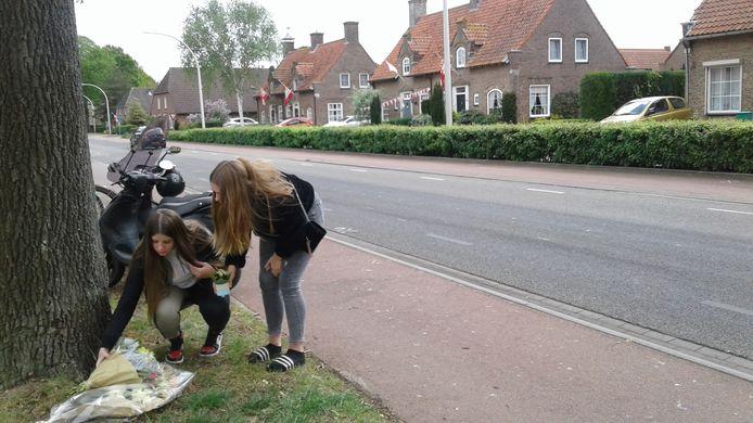 Leilah Spierings (l) en Dana van den Berg gedenken met een bos bloemen en een plantje het overlijden van een Pools jongetje na een verkeersongeval op de Bosscheweg.