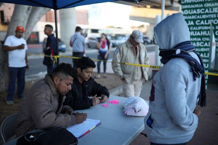 Joel Collado helpt andere migranten met hun registratie in het tentenkamp bij de grens. Beeld Felix Marquez