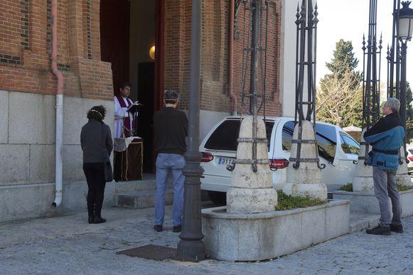 Priester Jose Antonio leidt een korte ceremonie op de begraafplaats van Almudena in Madrid.
